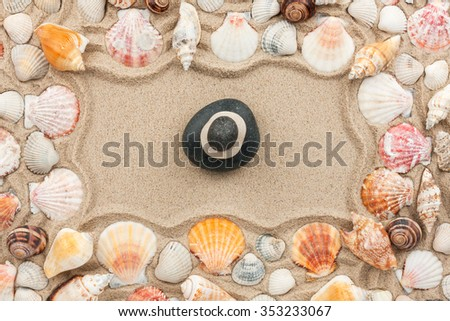 Rock cairn on the sand among sea shells, top view