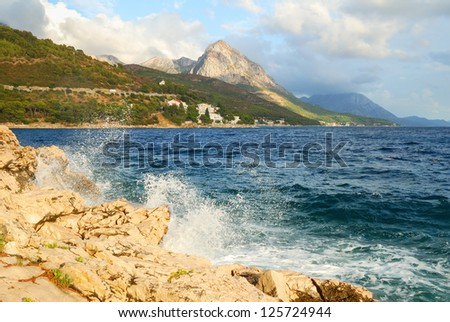 Rock Cliff Blue Sea Waves and a High Mountain - stock photo