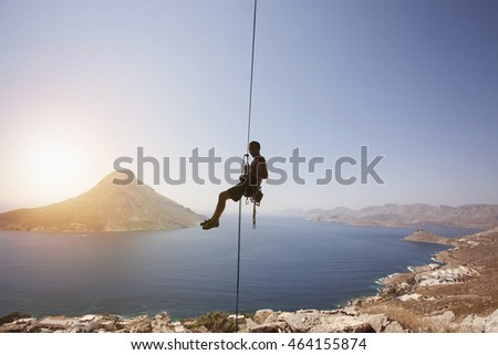 Rock climber against view of Telendos Island at sunset. Kalymnos Island, Greece