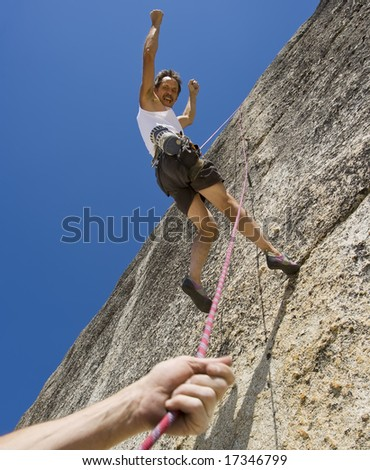 Rock climber being lowered by his partner with  their safety rope in Yosemite National Park, California, on a summer day.