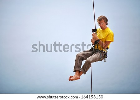 Rock climber belaying and being pulled up by another climber - stock photo