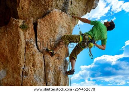 rock climber climbs on a rocky wall - stock photo