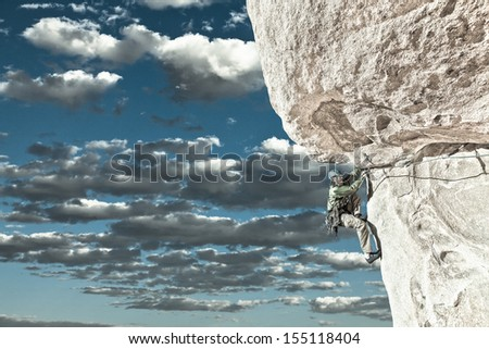 Rock climber clings to the edge of a challenging cliff in Joshua Tree National Park. - stock photo