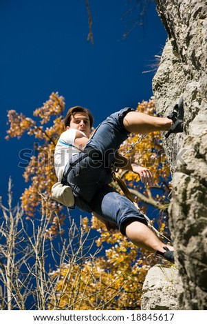 Rock Climber hanging in the cliff looking down