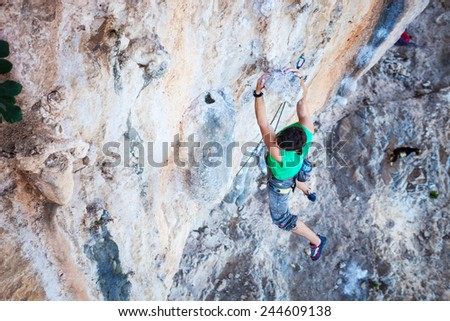 Rock climber holding on handhold while climbing cliff - stock photo