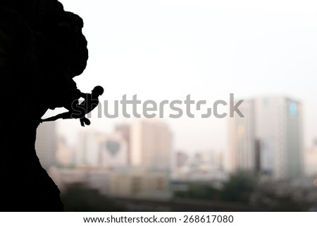 Rock climber on background of city. Sport and active life - stock photo