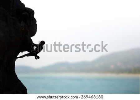 Rock climber on background of sea and sunshine. Sport and active life - stock photo