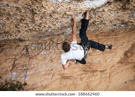 Rock climber on his challenging way up - stock photo
