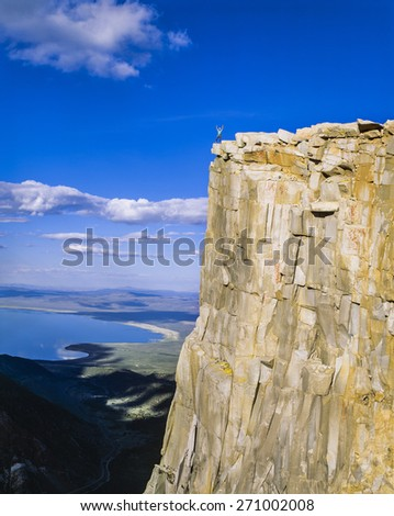 Rock climber on the summit after a challenging ascent. - stock photo