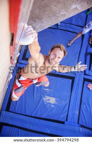 Rock climber participating in climbing competition, gripping top handhold