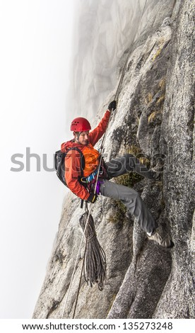 Rock climber rappels  on a challenging cliff. - stock photo