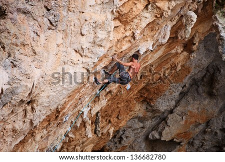 Rock climber struggling his way up - stock photo