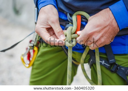 Rock climber wearing safety harness and climbing equipment outdoor, close-up image - stock photo