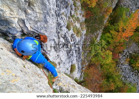 Rock climber woman balancing on vertical limestone route - stock photo