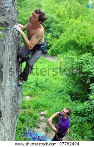Rock climbers. The leader is climbing up, the other climber belaying. - stock photo