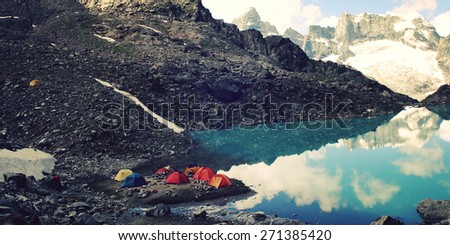 Rock Climbing camp vintage effect. Colorful tents at the Campground near Alpine Lake. Uzunkol, Caucasus Mountains, Karachay-Cherkessia, Russia. - stock photo