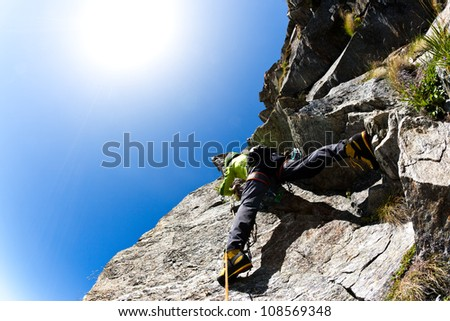 Rock climbing: climber on a steep wall. Clear sky, day light. West italian Alps, Europe. - stock photo
