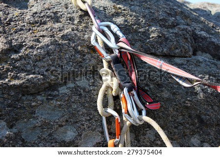 Rock climbing rope with hooks on  rock, close-up - stock photo