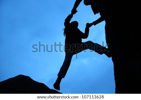 Rock climbing silhouette, gets a helping hand to get up - stock photo