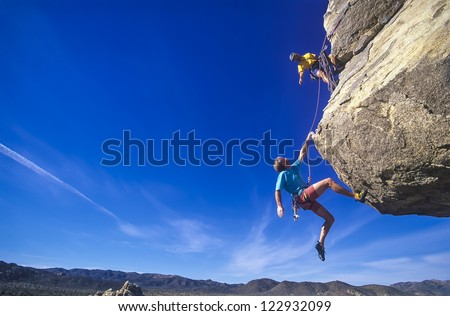Rock climbing team struggle for success on a challenging ascent.