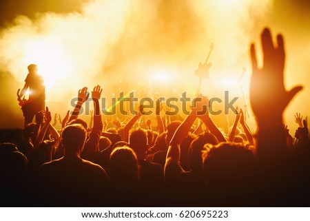 Rock concert, cheering crowd in front of bright colorful stage lights, Hands up with pleasure from the show