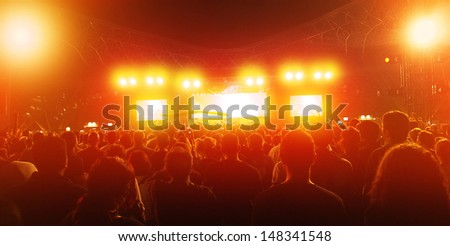 Rock concert, crowd of young people enjoying music in nightclub, holiday celebrations, dance club, red illumination, active lifestyle - stock photo
