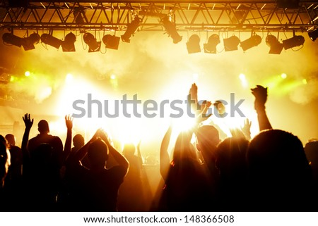 Rock concert, silhouettes of happy people raising up hands - stock photo