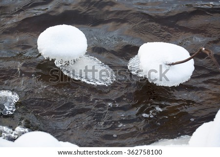 Rock covered by ice on a river during cold winter day.  - stock photo