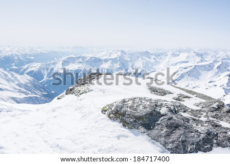 Rock covered with snow with mountain in the back, view from Ankogel, Austria - stock photo