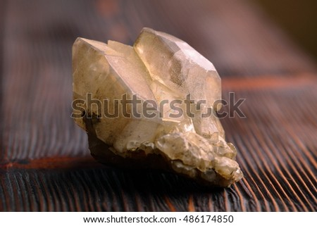 Rock crystal mineral stone on the wooden background. Quartz variety.