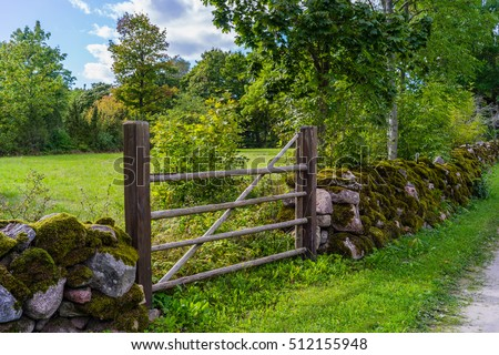 Rock fence and a wooden gate at the meadow