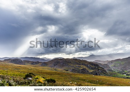 Rock formation landscape in Kerry in Ireland with massive clouds and sun rays - stock photo