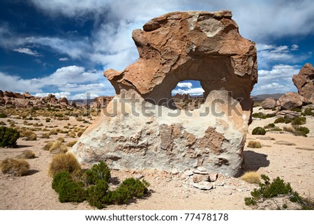 rock formation wind erosion sculptures sand stone and makes hole in stone eroded rock in Bolivian andes semi desert of the altiplano a landmark in the desolated landscape - stock photo