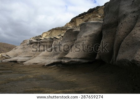 rock formations and caves housing exploited hippies, lunar landscape in Tenerife, Houses dug into the volcanic rock by the sea, Pumice, nudist beaches of Tenerife,abstract landscape with cloudy sky