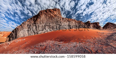 Rock formations and sand dune in the desert of Death Valley (Valle de la Muerte), San Pedro de Atacama, Chile. - stock photo