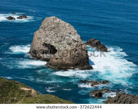 Rock formations in the ocean at New Zealand coastline - stock photo