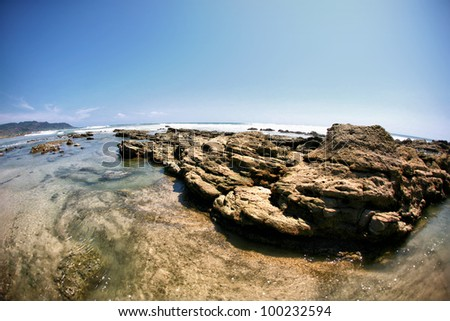 Rock formations in the ocean with wave approaching and blue sky