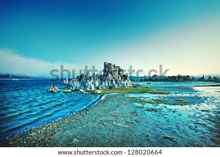 Rock formations in water at sunrise by mountain beach - stock photo