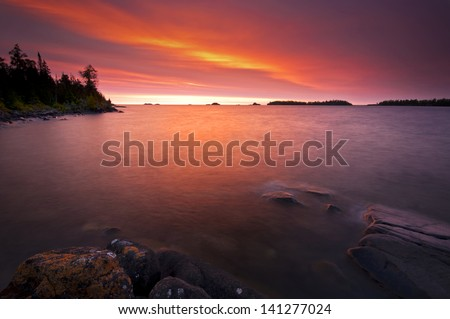 Rock Harbor Sunrise Sunrise colors reflect off the waters of Rock Harbor at Isle Royale National Park, Michigan. - stock photo