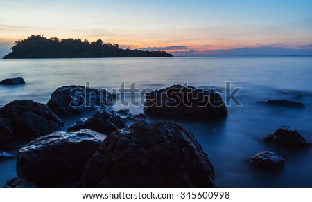 Rock in blue sea at sunset  - stock photo