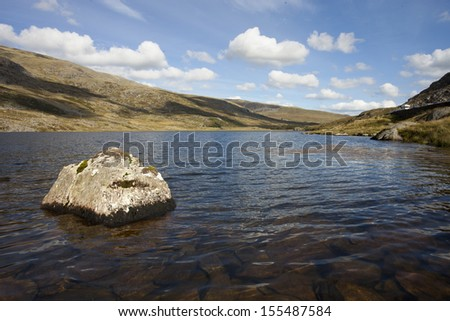 rock in water at a big lake in snowdonia, north wales - stock photo