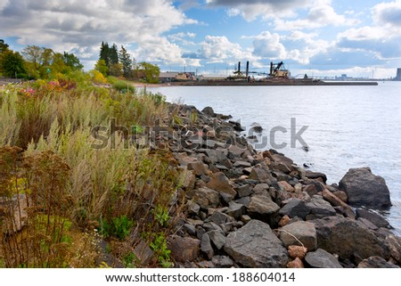 Rock Lakeshore in Duluth Harbor Basin with Shipping Boats in the Background. Duluth Minnesota - stock photo