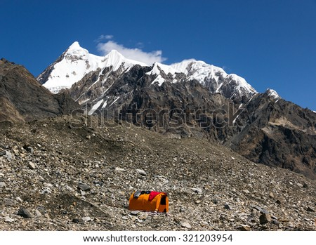 Rock Moraine High Peak View and Single Tent Base Camp of High Altitude Expedition at Mountains with Snow and Ice Summit Orange Bivouac with Sleeping Bags Drying on Roof of It - stock photo