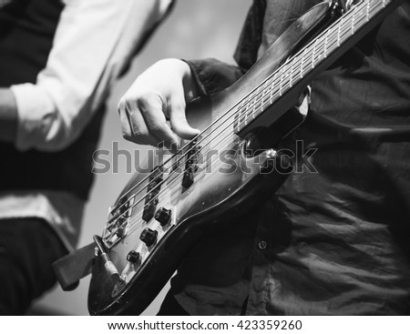 Rock music black and white background, bass guitar player, closeup photo with selective focus, selective focus - stock photo