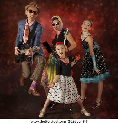 Rock musician family have fun playing music and singing on a black background with glowing lights - stock photo