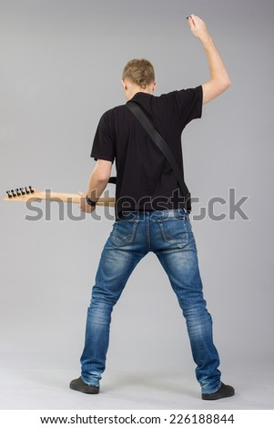 Rock musician is playing electrical guitar. - stock photo