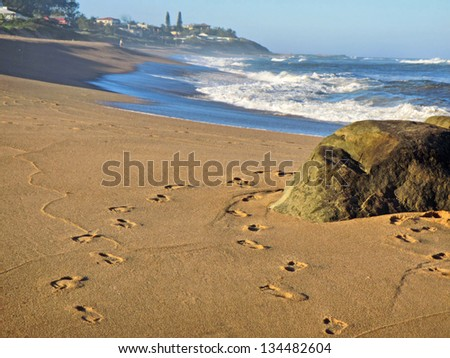Rock on beach and footprints on sand. Shot near Ballito and Durban, North Coast of Kwazulu-Natal, South Africa. - stock photo