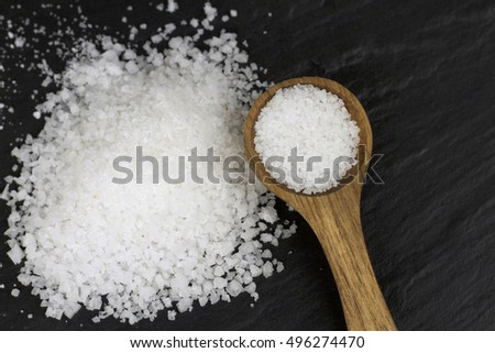 Rock Salt and wooden spoon on black stone background. Macro shot.