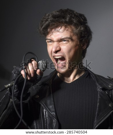 Rock singer screaming on the microphone - stock photo