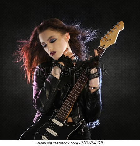 Rock star posing with her guitar - stock photo